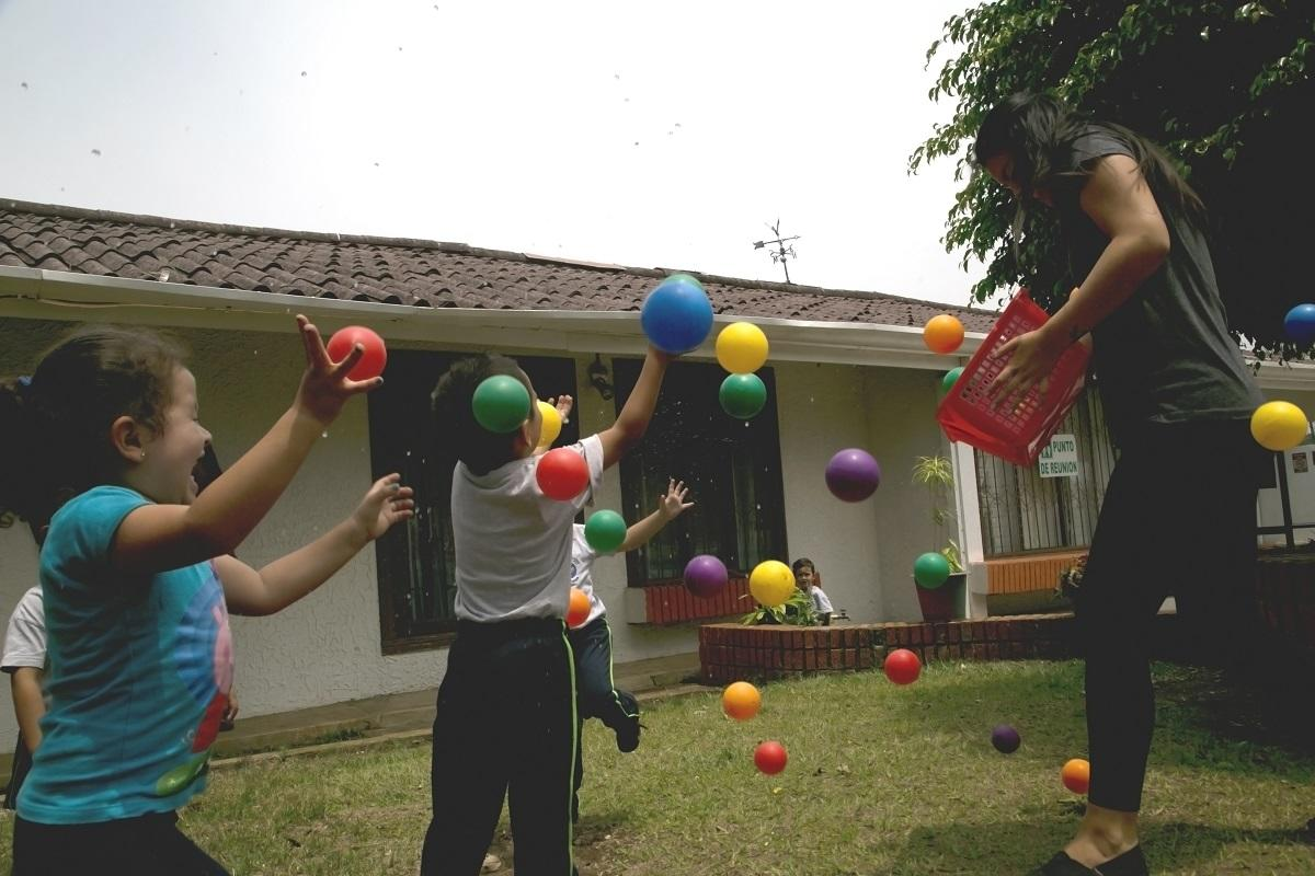Volunteers and the children play with colourful balls as part of their Childcare volunteer work in Costa Rica